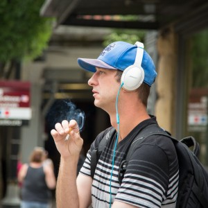 Portland Downtown Guy smoking a Cigarette with Headphones on